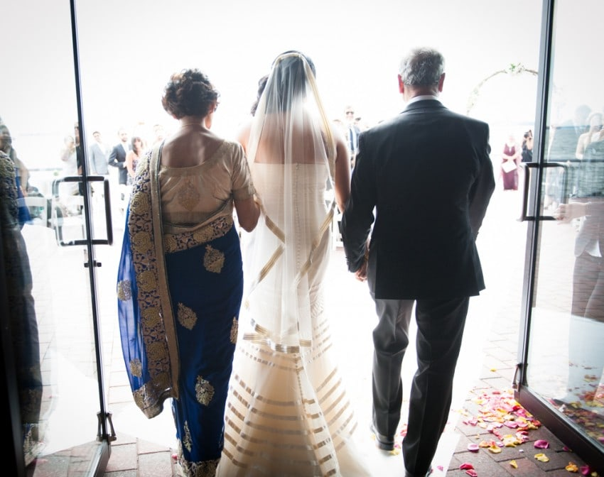 Bride walking down the aisle with parents at Brooklyn wedding